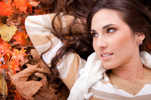 brunette woman lying on autumn leaves