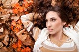 young woman lying on autumn leaves
