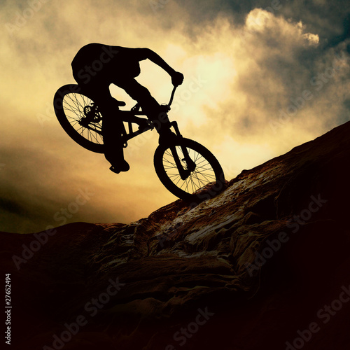 Silhouette of a man on muontain-bike, sunset © Andrii IURLOV