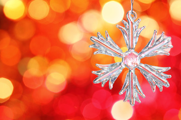 Glass snowflake against red blurred background