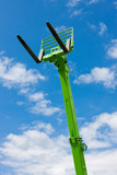 Green Telescopic Hydraulic Forks Towering Against Bright Blue Sk poster