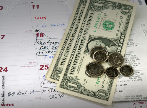 Receipts with dollar bills and coins on the monthly planner