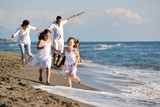 happy family playing with dog on beach - Fine Art prints