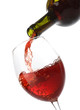 Pouring red wine into a glass isolated on white