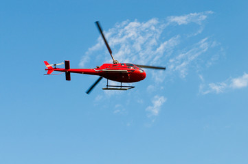 Red helicopter on the bright summer day