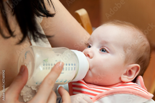 a mother is feeding her baby from a bottle