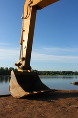 Hydraulic excavator arm with a bucket against a blue sky