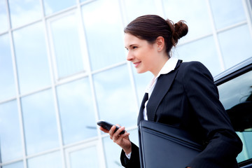 Business woman outside with mobile phone, smiling