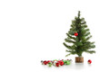 Small artificial tree with ornaments on white