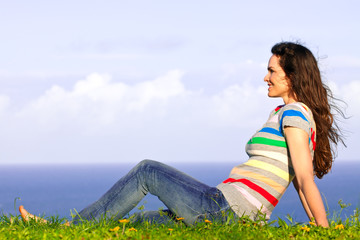 A beautiful young woman relaxing in the grass by the ocean