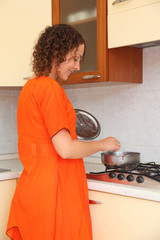 beautiful young woman standing in kitchen and prepare food