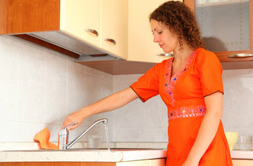 woman standing in kitchen. She opens faucet.