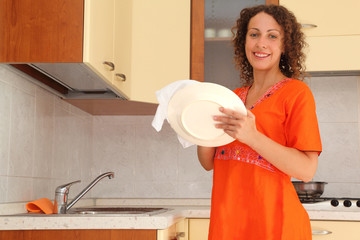 young woman standing in kitchen and wipes clean utensils
