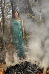 woman posing with leaves burning