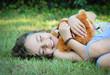 allongée dans l'herbe avec sa peluche