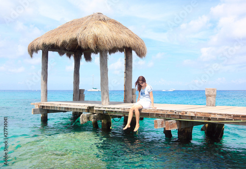girl sitting on a wooden pier in the caribbean