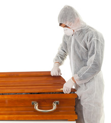 exhumation - man in protective workwear with coffin