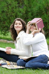 two student girls with books and laptop on natural background