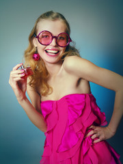 The laughing beautiful girl in pink glasses