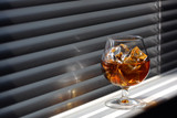 Whisky glass with ice on a window sill poster