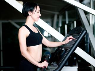 Femme faisant du sport - reglant le tapis de jogging