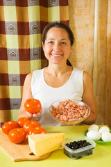 Woman with food products for farci tomato.  See series