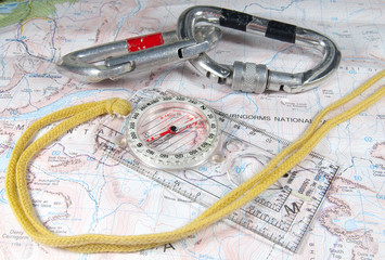 compass and climbing gear on map