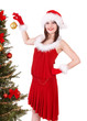 Girl in santa hat decorating christmas tree. Isolated.
