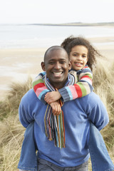 Father And Daughter Amongst Dunes On Winter Beach