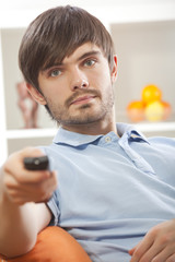 man with television remote at home