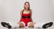 Sexy Santa helper girl in Christmas costume lying down over gray