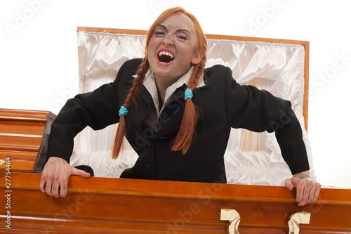 vampire woman in black clothes gets up from coffin