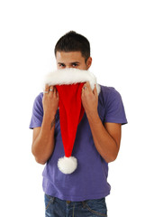 Young hispanic man hiding behind a Santa Hat
