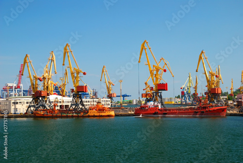 Leinwanddruck Bild The trading seaport with cranes, cargoes and ship