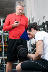 Young man with instructor at gym