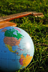 Globe and guitar in the grass
