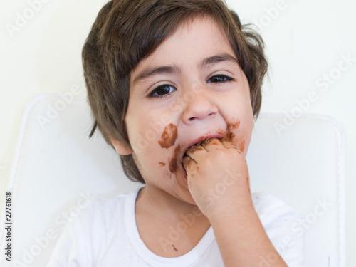 bambino con mani in bocca piene di cioccolato