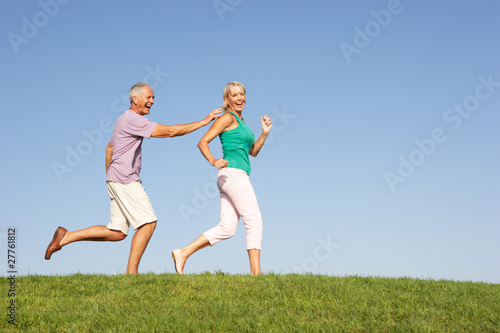 Senior couple running through field