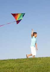 Young boy runs with kite through field