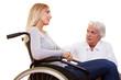 Ärztin redet mit Rollstuhlfahrerin