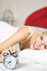 Young happy smiling woman with alarmclock on the bed