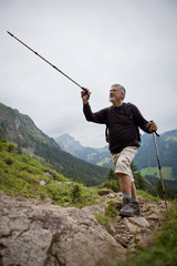handsome senior man showing direction with his hiking stick whil