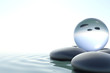 Zen stones and glass sphere on white background