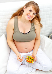 Happy beautiful pregnant woman sitting on sofa  with fruit salad