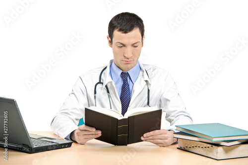 A male doctor reading a book in his office