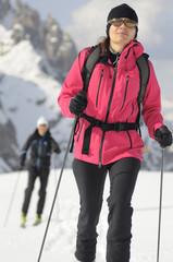 sportliche Frau mit Skitouren durch frischen Schnee.