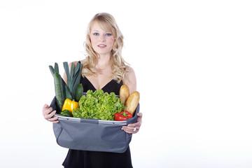 Hübsche blonde Frau mit Einkaufstasche, Obst und Gemüse, quer