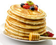 stack of pancakes with honey and berries
