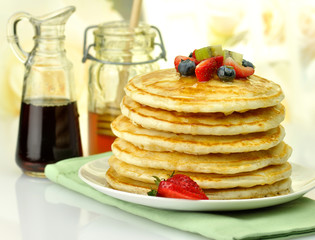 stack of pancakes with maple syrup,honey and berries