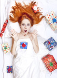 Surprised red-haired girl in bed with Christmas gifts.